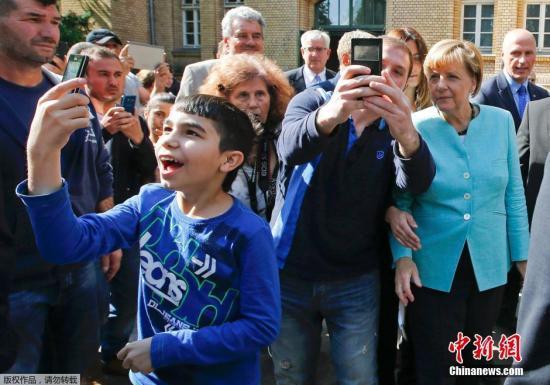 当地时间2015年9月10日,德国柏林,德国总理默克尔慰问抵达德国寻求避难的难民。